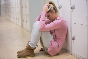 Upset student sitting on floor of hallway against lockers